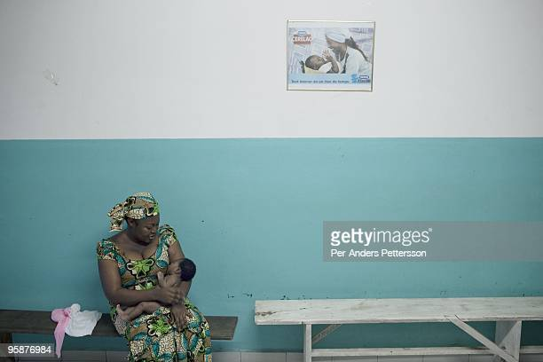 A woman sits with her baby at the maternity ward at Bonassama hospital on August 10 2009 in Douala Cameroon The ward is full of advertising for...