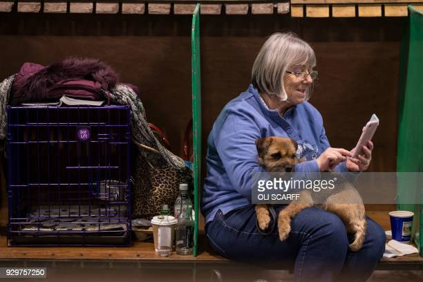 Woman sits with her Border Terrier dog on the second day of the Crufts dog show at the National Exhibition Centre in Birmingham, central England, on...