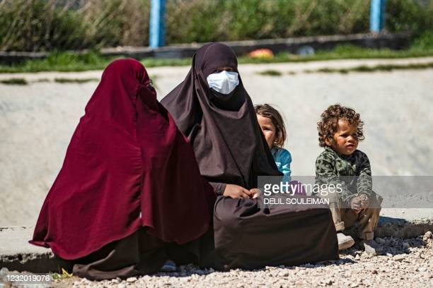 Woman sits with her child on the ground at Camp Roj, where relatives of people suspected of belonging to the Islamic State group are held, in the...