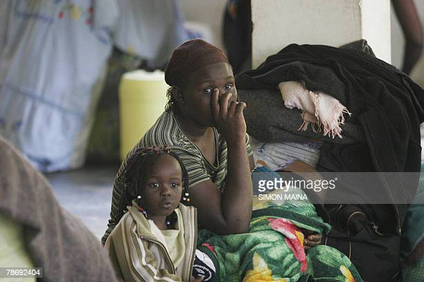 A woman sits with her children in their new shelter at the Jamhuri grounds in Nairobi 02 January 2008 where they have spent three days after fleeing...