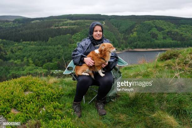 A woman sits with her dog as spectators gather on a hillside above Derwent Dam as they wait for a Lancaster bomber from the Battle of Britain...