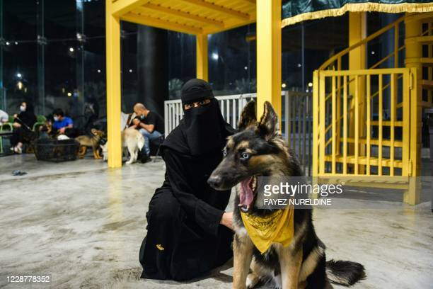 """Woman sits with her German Shepherd at the """"Barking Lot"""" cafe in Saudi Arabia's eastern Gulf city of Khobar, 450 kilometres east of the capital, on..."""