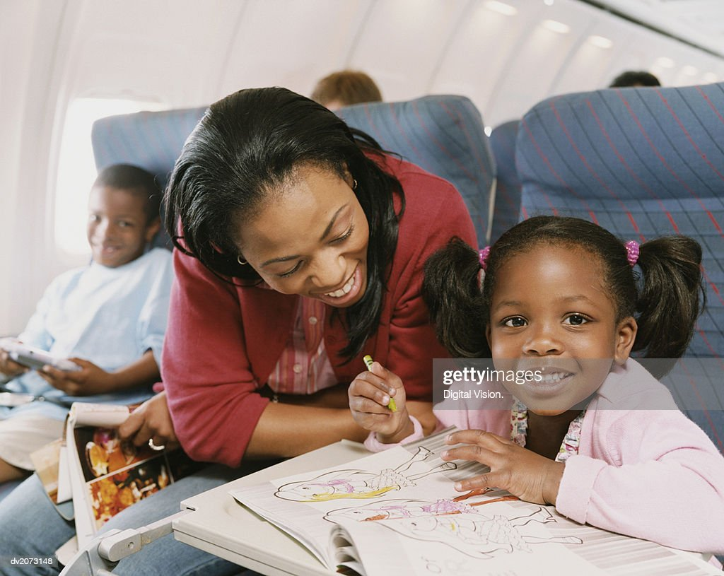 Woman Sits With Her Young Daughter on a Plane, Watching Her Draw in Her Colouring-In Book : Stock Photo