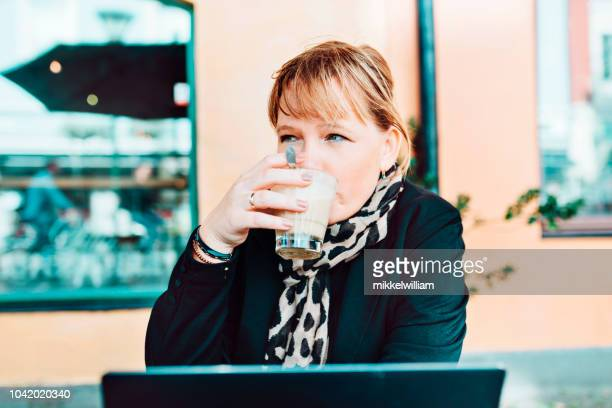 Woman sits with laptop at outdoor cafe drinking coffee