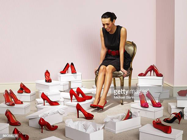 Woman sits with red shoes surrounding her