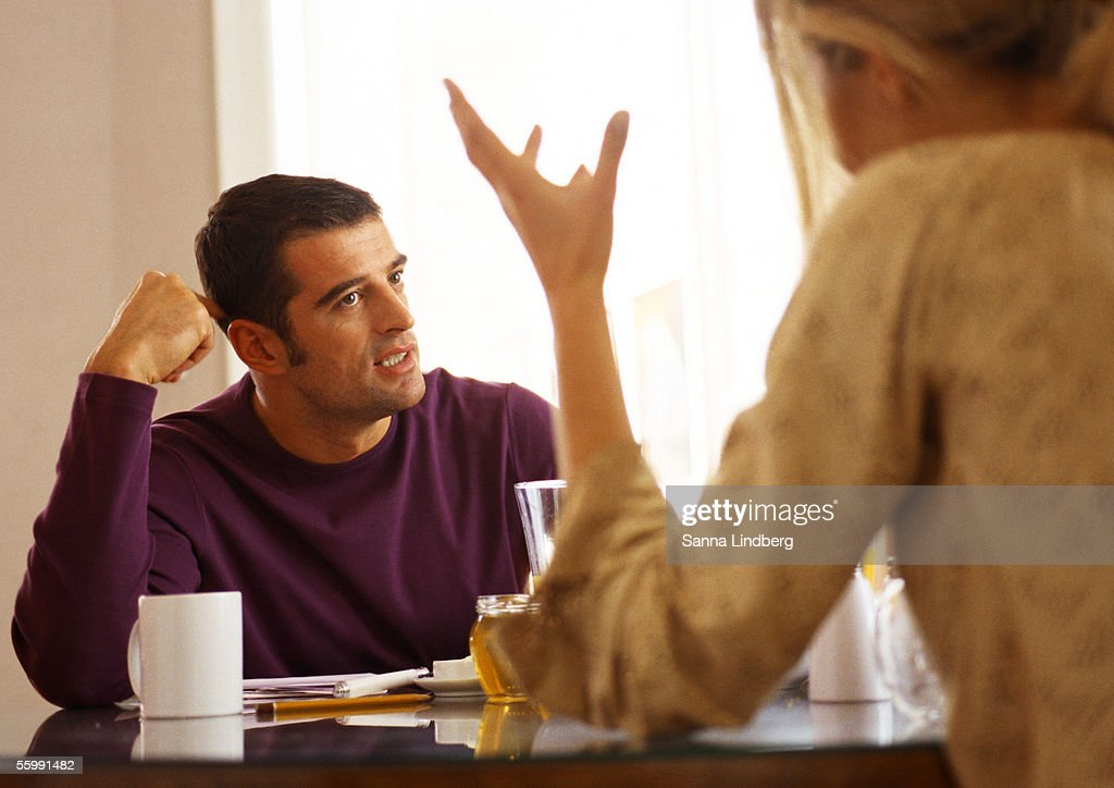 Woman sitting across from man at table, rear view. : Stock Photo