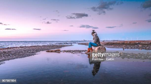 Woman Sitting Against Sea During Sunset