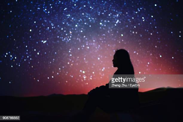 woman sitting against sky at night - astronomy stock pictures, royalty-free photos & images