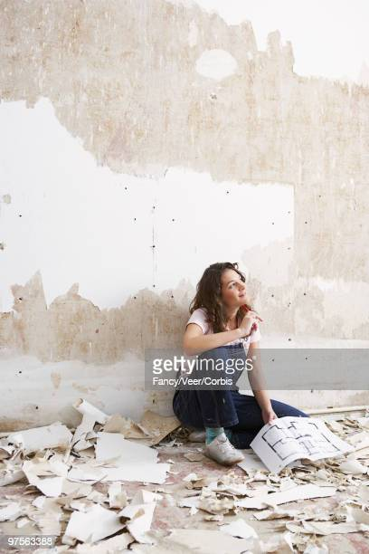 woman sitting against wall with floor plans - renovierung themengebiet stock-fotos und bilder