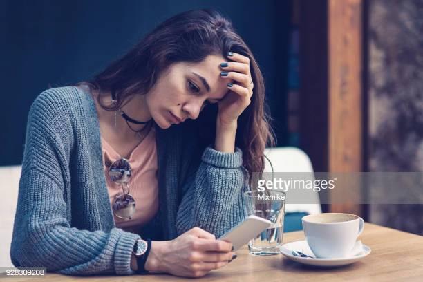 Frau sitzt alleine im Café und SMS auf ihr Handy