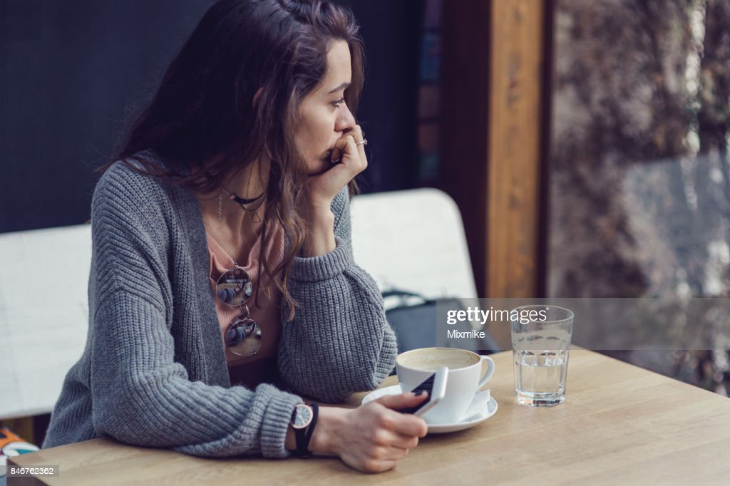 Woman sitting alone, having coffee and texting on her mobile phone : Stock Photo