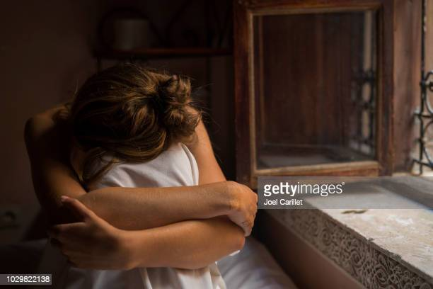 woman sitting alone in bedroom with head on knees - unrecognizable person stock pictures, royalty-free photos & images