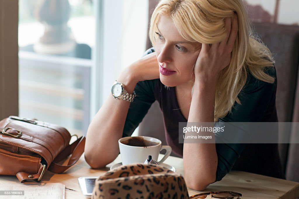 Woman sitting alone in cafe : Foto stock