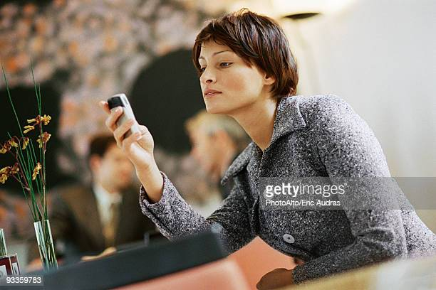 Woman sitting alone in restaurant, looking at cell phone