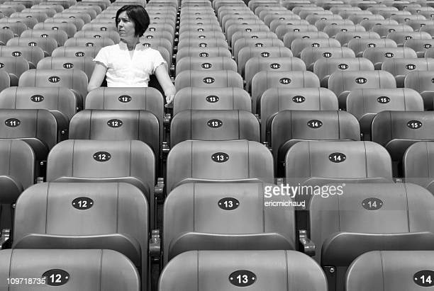 Woman Sitting Alone in Stadium Chairs, Black and White