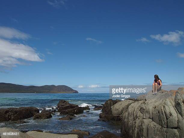 Woman sitting alone on rocks beside the ocean