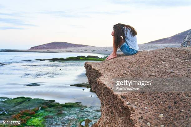 Woman sitting alone on the rocks at the beach on January 18 2018 in El Medano Tenerife Spain Model released