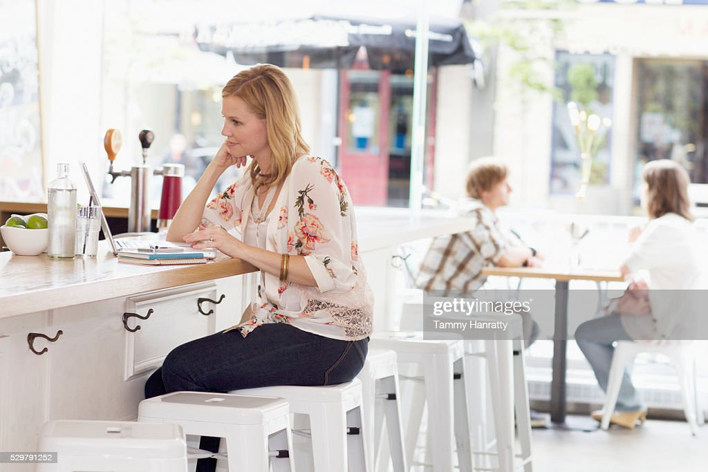 Woman sitting and bar counter and using laptop : Stock-Foto