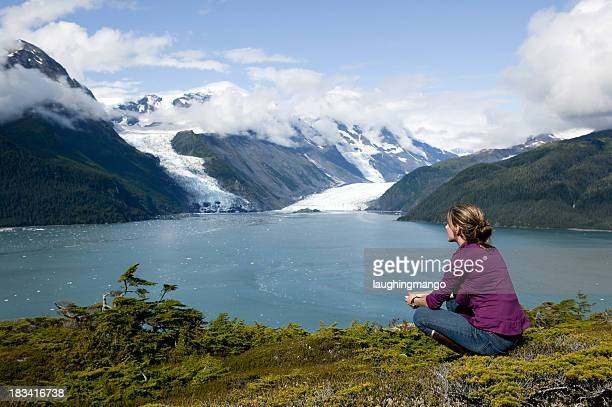 Woman sitting and gazing at water and snowy hills in Alaska