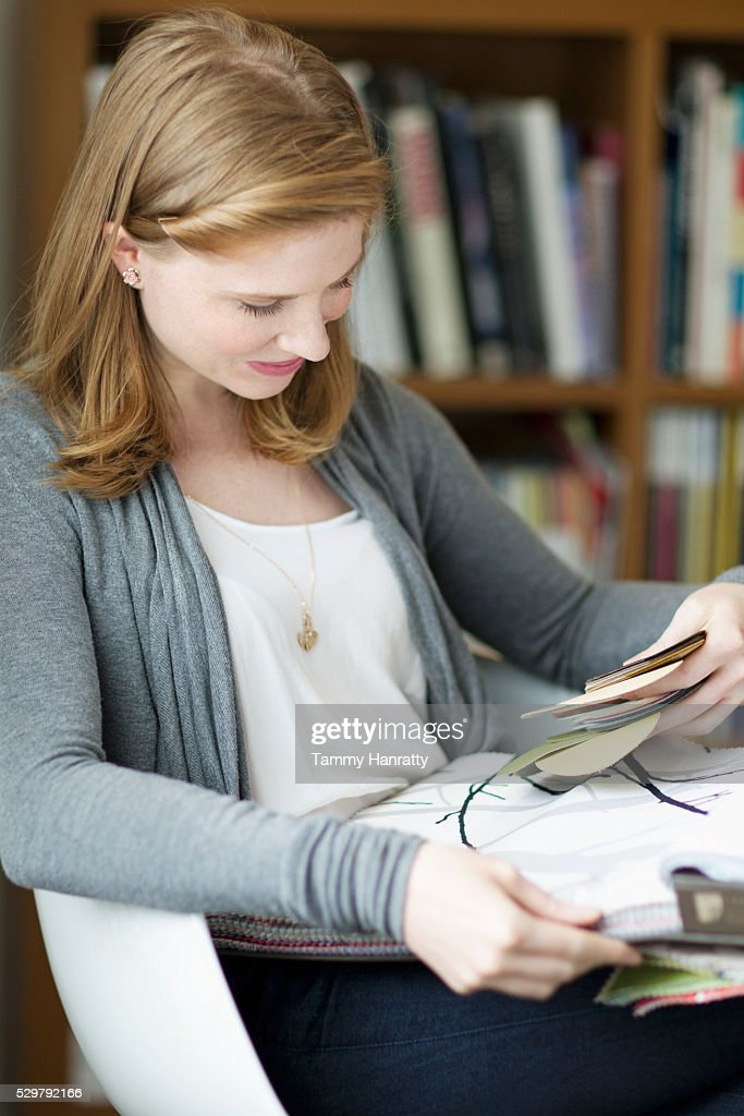 Woman sitting and looking at samples : Stock-Foto