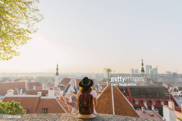 woman sitting and looking at tallinn in the morning - estonia stock pictures, royalty-free photos & images