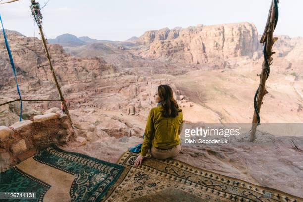 woman sitting and looking at view of desert in petra - jordan middle east stock pictures, royalty-free photos & images