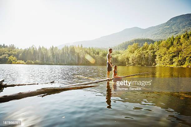 Woman sitting and man standing on logs in lake