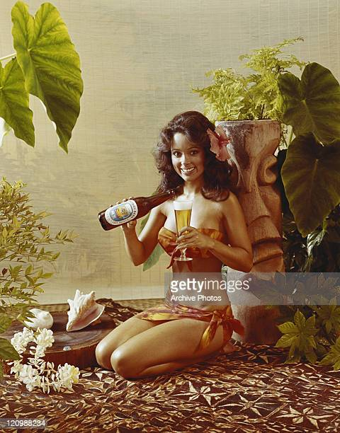 Woman sitting and pouring beer into glass smiling portrait