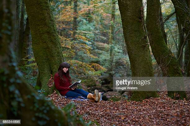 Woman sitting and reading book in Autumn woodland.