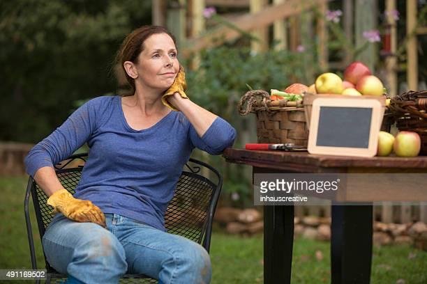 Frau sitzt und entspannen Sie bei der Arbeit in Ihrem Garten.