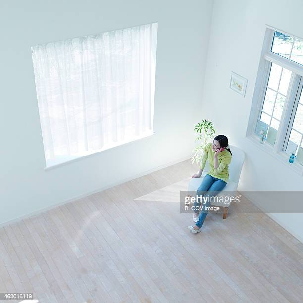 woman sitting and talking on phone - tidy room stock pictures, royalty-free photos & images