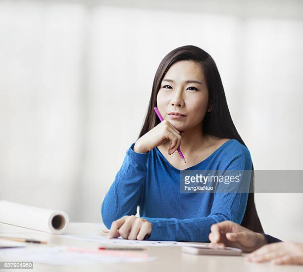 woman sitting and thinking in design studio office - real estate office stock photos and pictures