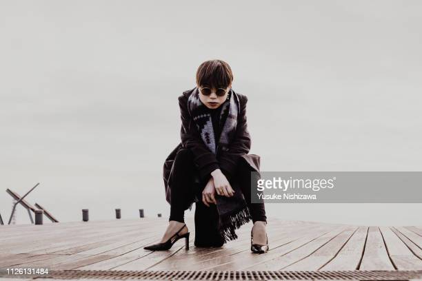 a woman sitting and watching here - yusuke nishizawa stock-fotos und bilder