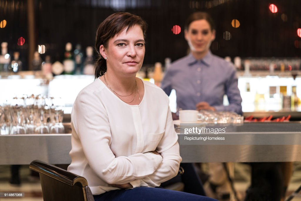 Eine Geschäftsfrau sitzt locker mit verschränkten Armen an einer Bar : Stock-Foto