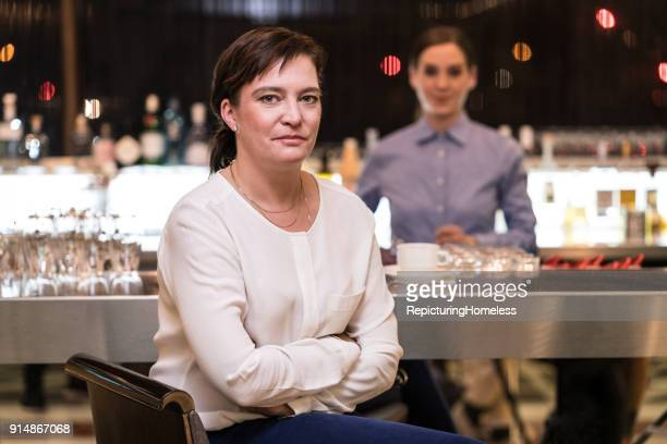 Eine Geschäftsfrau sitzt locker mit verschränkten Armen an einer Bar