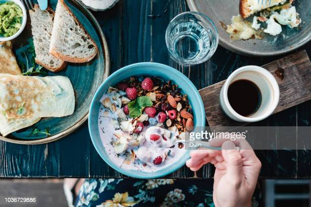 woman sitting at a breakfast table eating oatmeal with raspberries, nuts and seeds - 盛り付け ストックフォトと画像
