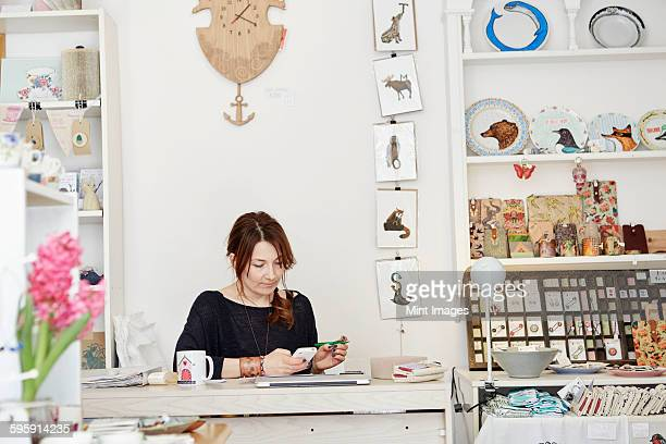 A woman sitting at a desk in a small gift shop, doing the paperwork, managing the business, using a laptop and a smart phone.
