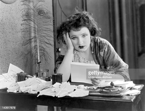 A woman sitting at a desk with her head in her hand looking depressed with a pile of papers early to mid 1920s
