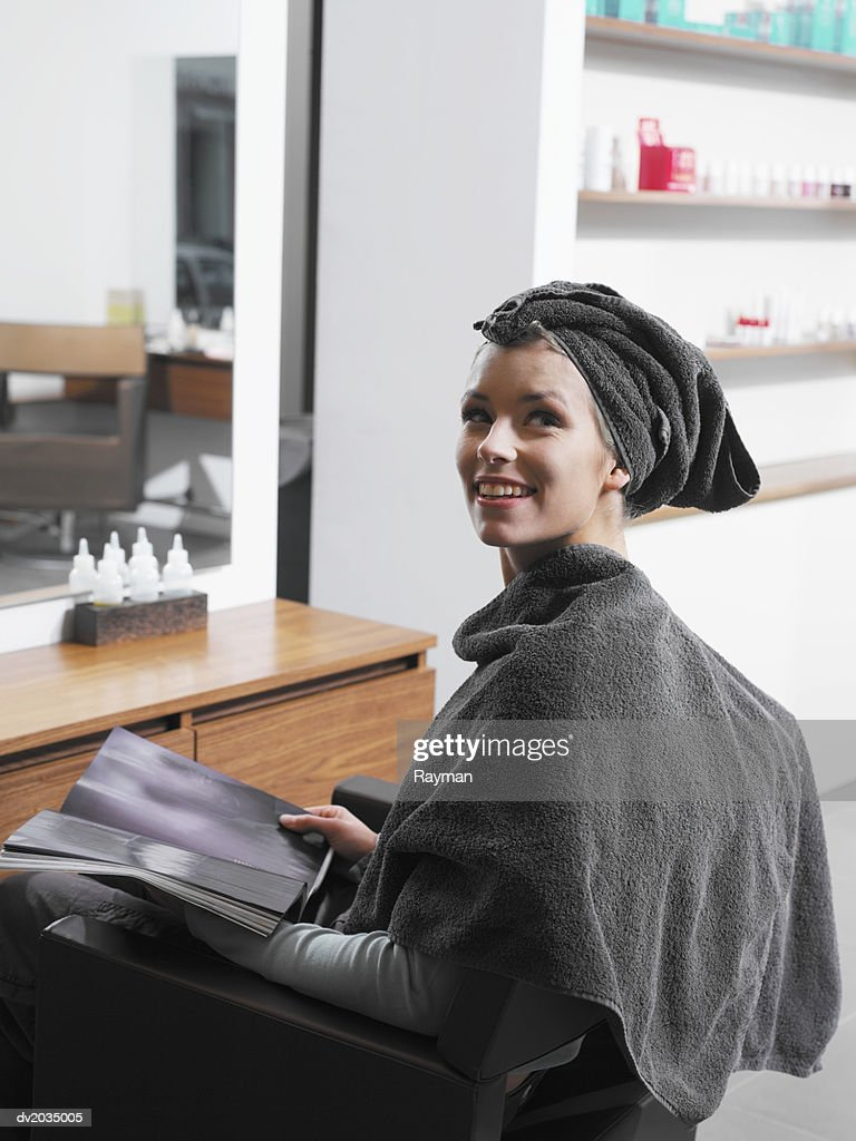 Woman Sitting at a Hair Salon With Her hair Wrapped in a Towel : Stock Photo