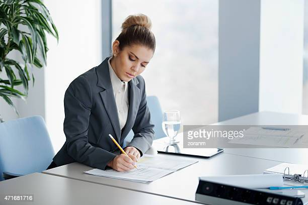 A woman sitting at a large table taking notes with a pencil