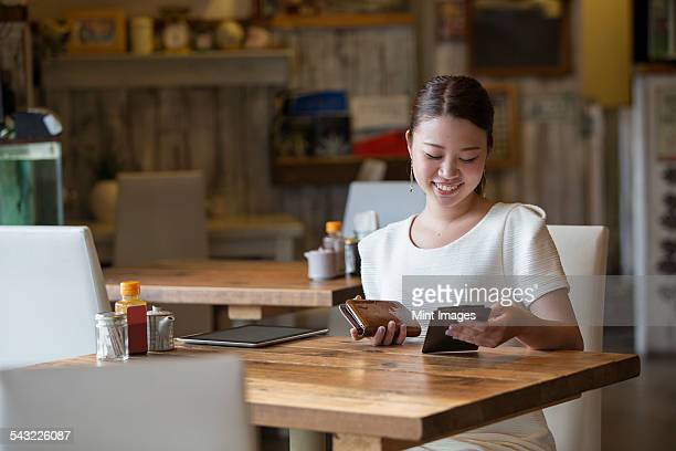 Woman sitting at a table in a cafe, holding the bill and her purse, smiling.