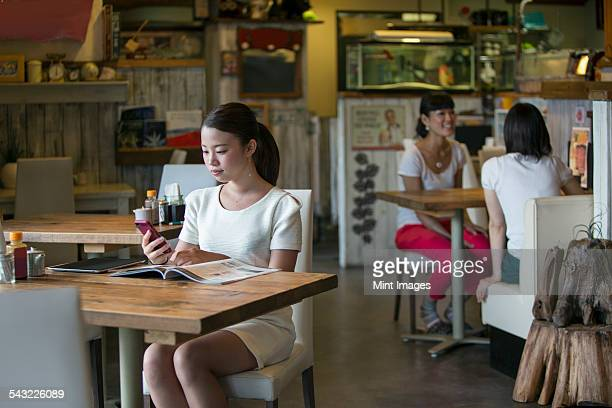 Woman sitting at a table in a cafe, looking at her mobile phone, two women at a table in the background.