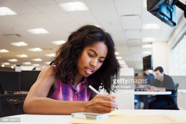 A woman sitting at a table in an office writing.