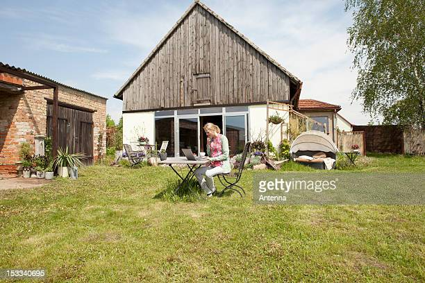 A woman sitting at a table in her backyard using a laptop