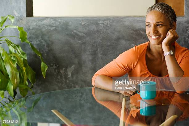 woman sitting at a table with a mug smiling - 45 49 years stock pictures, royalty-free photos & images