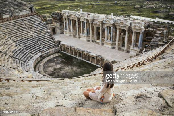woman sitting at amphitheater - amphitheatre stock photos and pictures