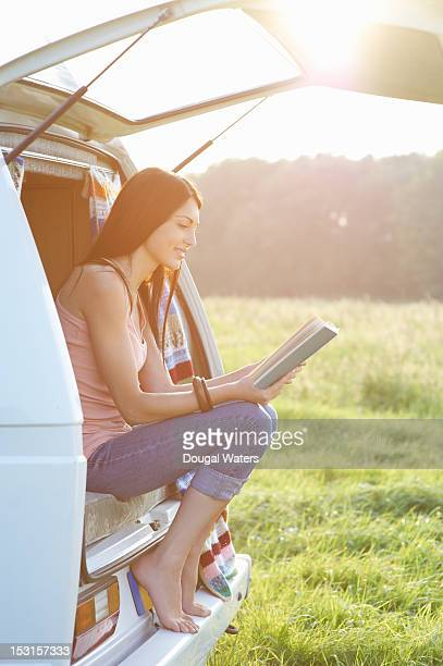 Woman sitting at back of camper van reading book.