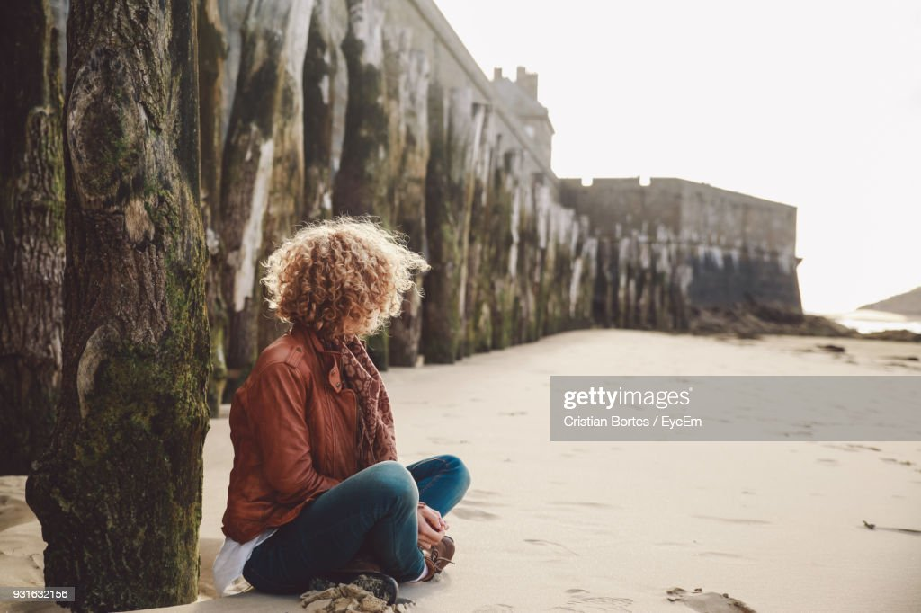 Woman Sitting At Beach Against Castle : Stock Photo