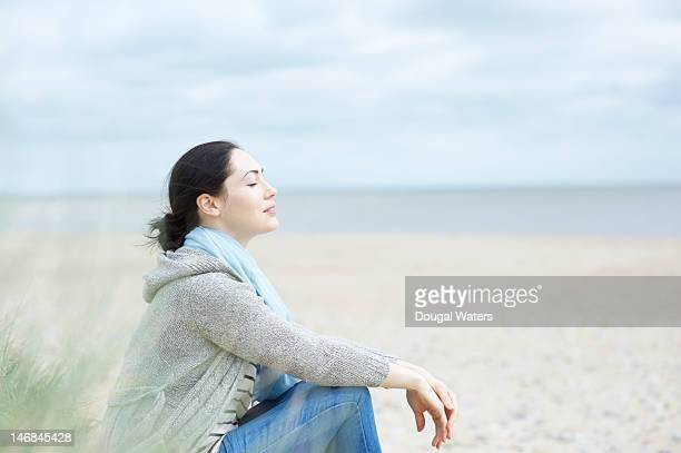 Woman sitting at beach with eyes closed.
