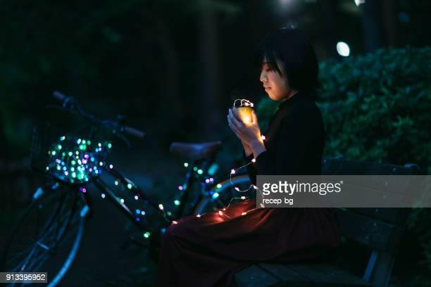 Frau sitzt auf Bank mit LED-Leuchten